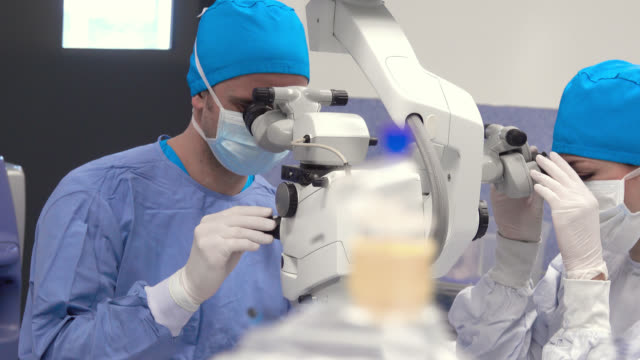 surgeon and nurse operating using a surgical microscope - operating stock videos & royalty-free footage
