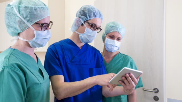surgeon and nurses in operating room - fürsorglichkeit stock-videos und b-roll-filmmaterial