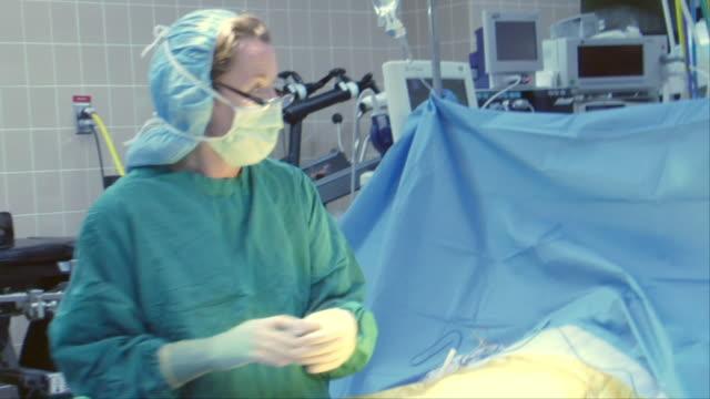 stockvideo's en b-roll-footage met ms, shaky, surgeon and nurses preparing patient for surgery in operating room, berkeley, california, usa - operatiekamer