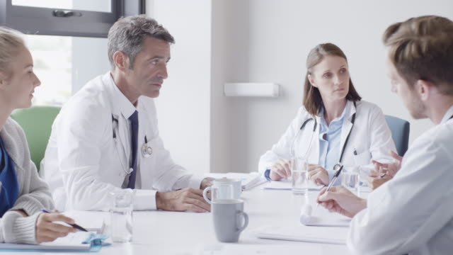 surgeon discussing with doctors during meeting - colleague stock videos & royalty-free footage