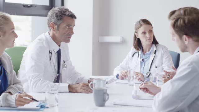 vídeos y material grabado en eventos de stock de cirujano discutiendo con los médicos durante la reunión - colega
