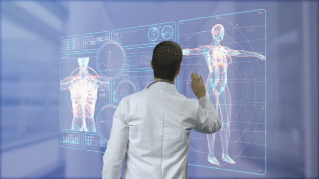surgeon doctor looking at futuristic medical charts at a high tech hospital - operation stock videos & royalty-free footage