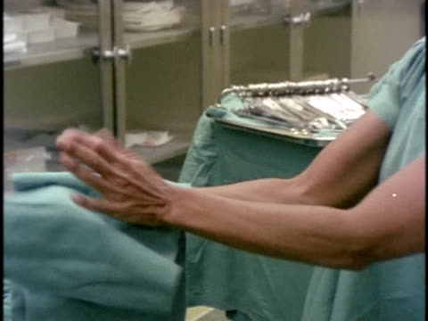 1978, cu zo ms surgeon getting dressed prior to operation, los angeles, california, usa - surgeon stock videos & royalty-free footage