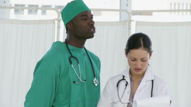 vídeos de stock e filmes b-roll de ms surgeon having discussion with nurse / cape town, south africa - bata cirúrgica