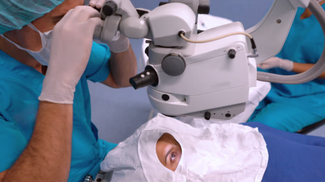 surgeon looking through a microscope in an optical surgery - operating stock videos & royalty-free footage