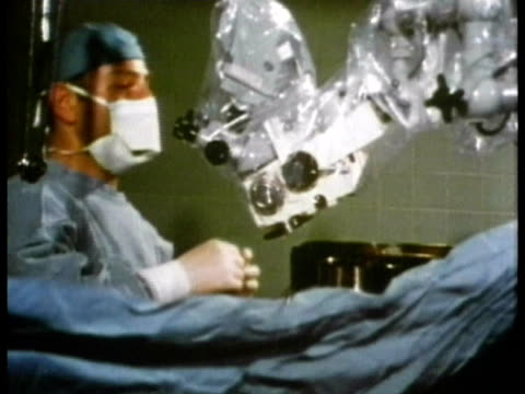 vidéos et rushes de 1969 ms surgeon looking through endoscope or microscopic camera during stapedectomy procedure in operating theatre/ usa/ audio - bloc