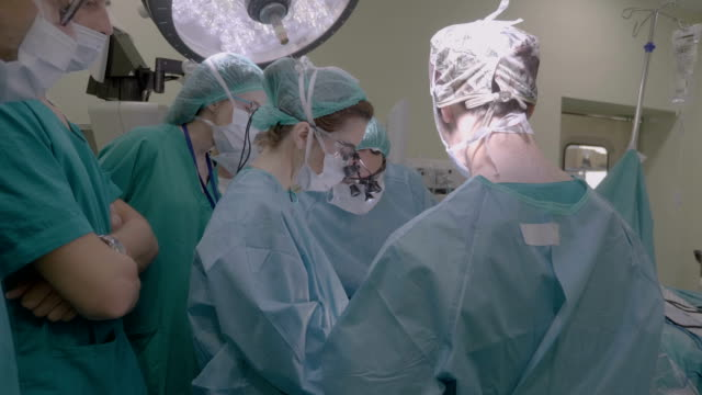 surgeon performing an operation in the surgery room - sala operatoria video stock e b–roll