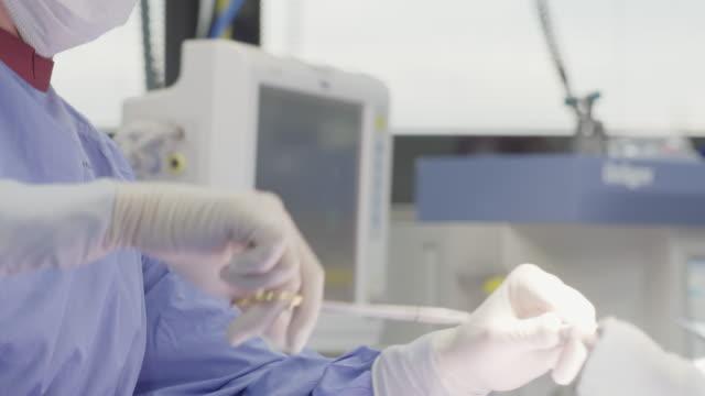vídeos y material grabado en eventos de stock de cirujano realizar la cirugía en quirófano - disposable gloves