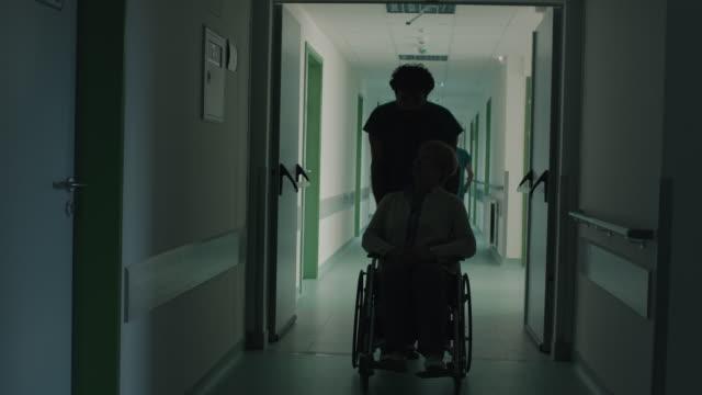 chirurgo che spinge la donna anziana in sedia a rotelle - pushing video stock e b–roll