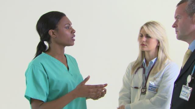 surgeon talking to colleagues - 手術服点の映像素材/bロール