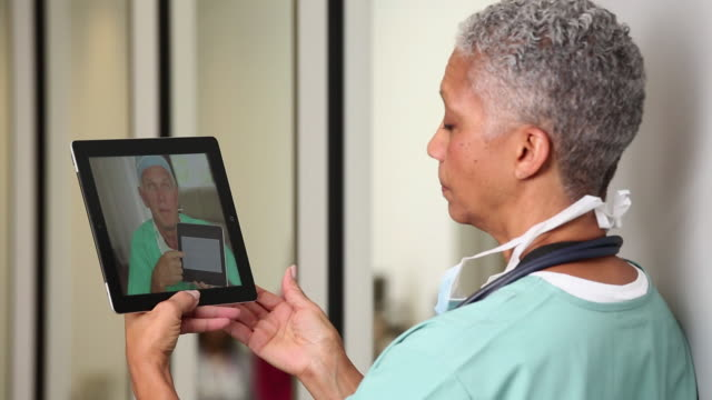 cu surgeon video conferencing with other doctors on tablet computer / richmond, virginia, usa - ostamerika stock-videos und b-roll-filmmaterial