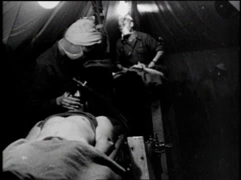 vidéos et rushes de surgeon washes hands / nurses prepare equipment / nurse prepares equipment / nurse drapes cloth over patient - world war 1