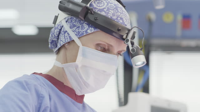 surgeon wearing head lamp and mask during surgery - surgeon stock videos & royalty-free footage