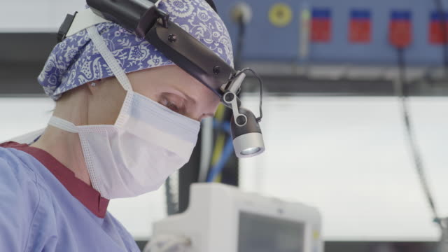 Surgeon wearing head lamp and mask during surgery