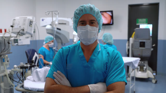 surgeon wearing protective gear at an operating room facing camera crossing arms while team prepares patient - protective glove stock videos & royalty-free footage