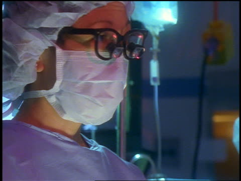 vídeos de stock e filmes b-roll de surgeon wearing surgical mask + eyeglasses with microscope attached looking down - bata cirúrgica