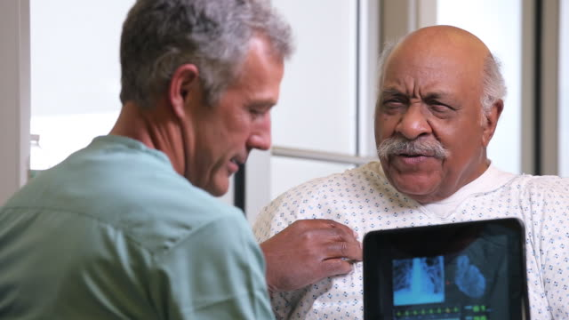 CU Surgeon with Tablet Computer, Talking to Senior Patient in Hospital Room / Richmond, Virginia, USA