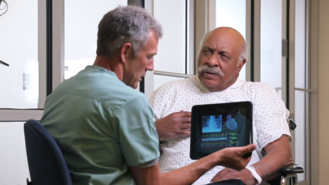 MS Surgeon with Tablet Computer, Talking to Senior Patient in Hospital Room / Richmond, Virginia, USA