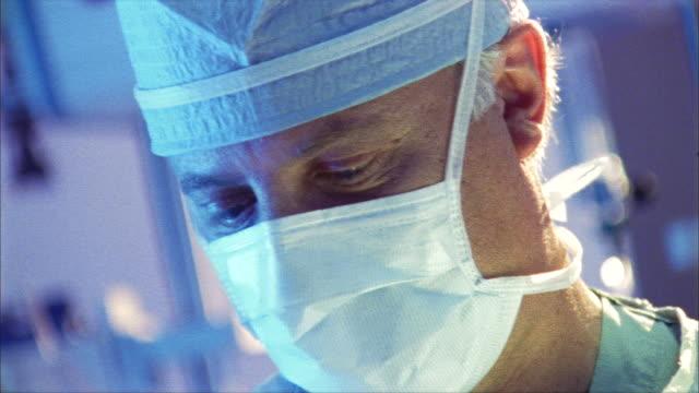ecu, selective focus, surgeon working in operating room, swedish american heart hospital, rockford, illinois, usa - surgeon stock videos & royalty-free footage