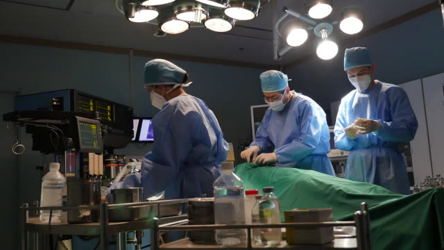 Surgeons and nurses operating a surgery on a patient