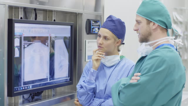 Surgeons discussing over x-ray in operating room