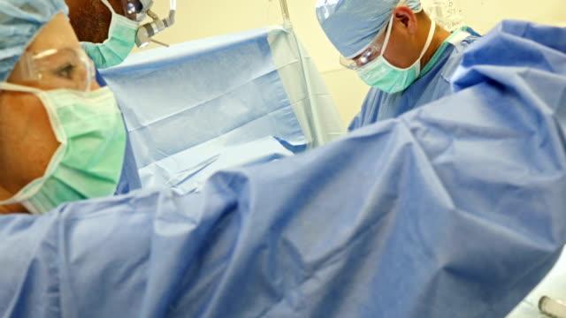 vídeos de stock e filmes b-roll de cirurgiões utilizar sobre o abdómen do doente, - bata cirúrgica