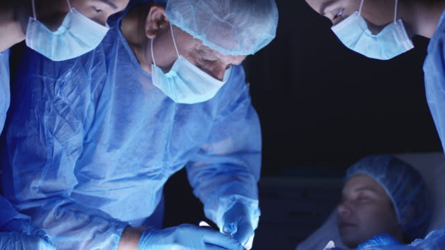 vídeos de stock e filmes b-roll de surgeons performing surgery - bata cirúrgica