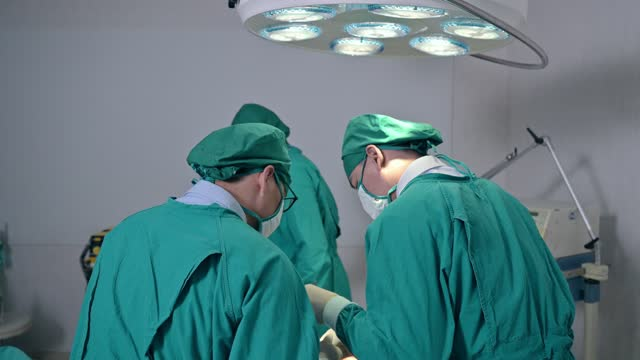 surgeons team in surgical gown performing surgery a seriously injured patient in operating room at hospital - operating gown stock videos & royalty-free footage