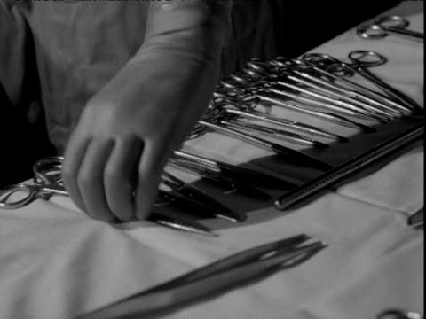 Surgery instruments on table surgeon and others at work UK 1955