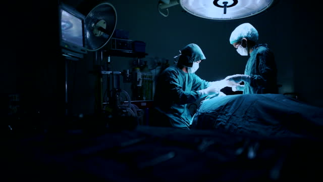 surgery team operating in a surgical room - operating stock videos & royalty-free footage
