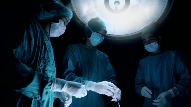 surgery team operating in a surgical room - scrubs stock videos & royalty-free footage