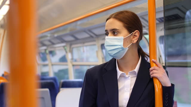 surgical mask commuter. young woman on a train. - interview event stock videos & royalty-free footage