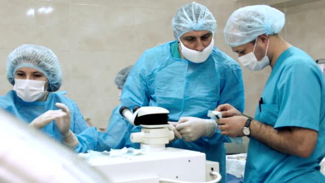 vidéos et rushes de équipe de chirurgien en salle d'opération - ressources humaines