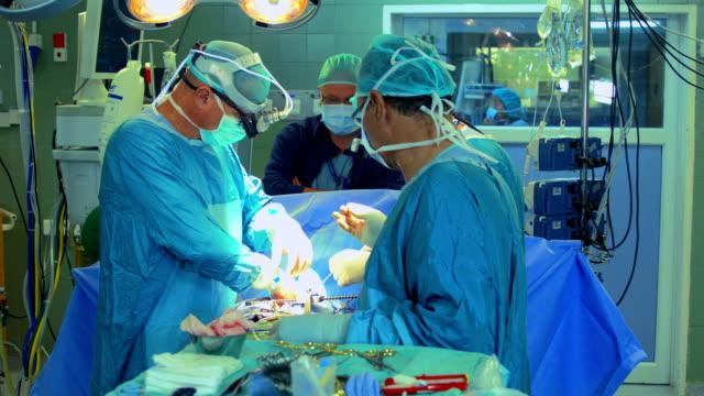 squadra chirurgica operativa sul cuore - sala operatoria video stock e b–roll