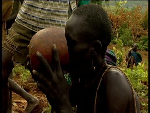 vídeos de stock e filmes b-roll de suri male drinks blood freshly drained from cattle in traditional ceremony suri territory ethiopia - corno de áfrica