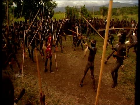 vídeos de stock e filmes b-roll de suri males gather ready for battle at donga stick fighting contest suri territory ethiopia - corno de áfrica