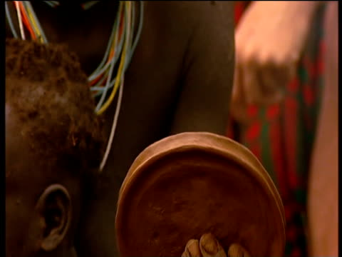 Suri woman clutches small child as she makes large clay lip plate Suri territory Ethiopia