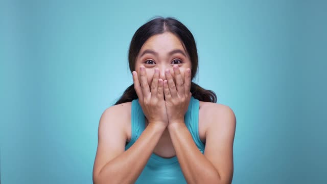 vídeos de stock e filmes b-roll de surprise happy woman on isolated blue background 4k - cheio