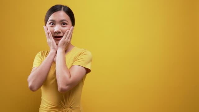 surprise woman look at camera  over yellow isolated background - plain background stock videos & royalty-free footage