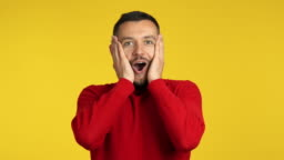 Surprised amazing man on yellow background