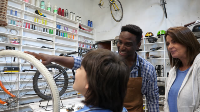 surprised little boy coming into a bicycle to buy his first bike with his mom looking very happy and salesman showing him a bicycle - salesman stock videos & royalty-free footage