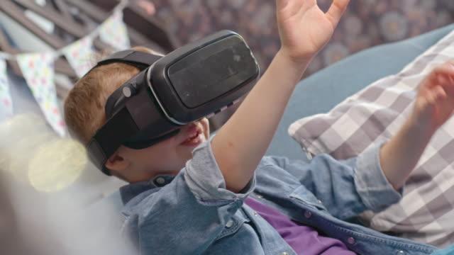 surprised little boy watching video vr glasses - セレクティブフォーカス点の映像素材/bロール