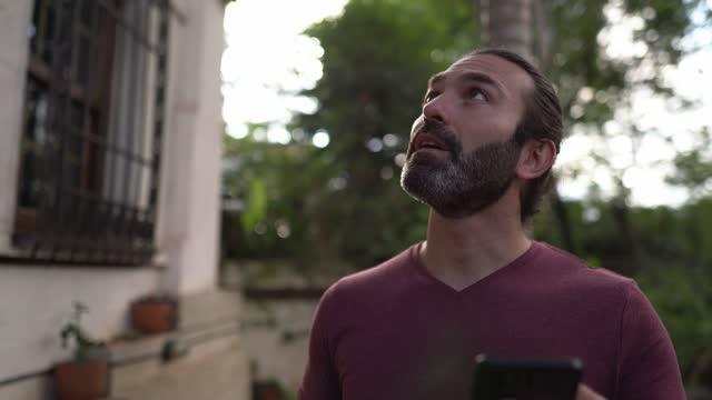 vídeos y material grabado en eventos de stock de hombre sorprendido buscando teléfono móvil y llegando al albergue - alojamiento y desayuno