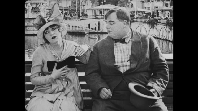 1917 Surprised man (Fatty Arbuckle) slides up to sick woman on bench and is concerned she will vomit in his hat