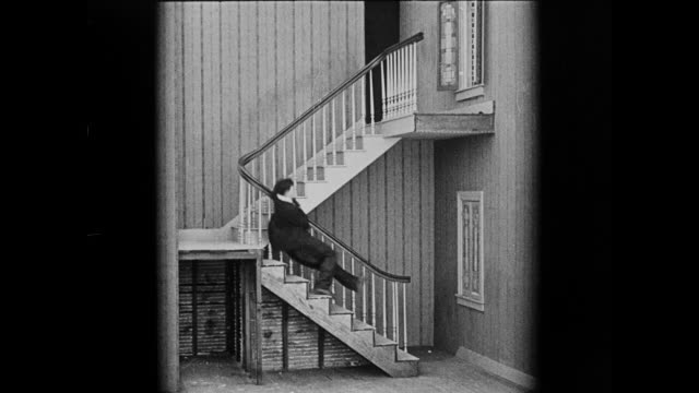 1920 surprised man (buster keaton) trips over his huge pants and slips down stairs - slapstick stock videos & royalty-free footage