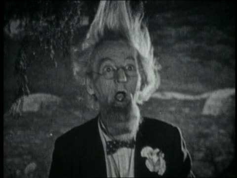 b/w 1920 surprised senior man in bowtie + hair standing straight up - sorpresa video stock e b–roll