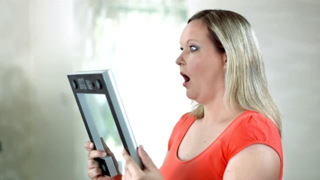 hd :dolly 驚く女性であるバスルームに体重計 - 体重計点の映像素材/bロール