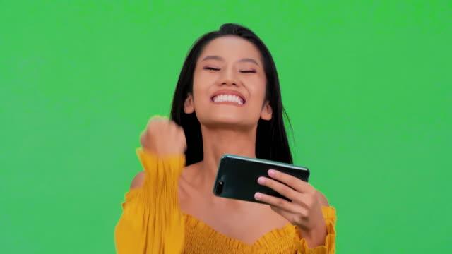 stockvideo's en b-roll-footage met verrast jonge zwarte vrouw met behulp van slimme telefoon geïsoleerd op groene achtergrond. portret van een gelukkige zwarte vrouw vieren met mobiele telefoon geïsoleerd over groene achtergrond. technologie concept. groen scherm - winnen