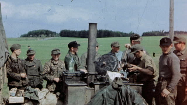 surrendered german army soldiers cooking food in outdoor kitchen one soldier very young / czechoslovakia - prigioniero di guerra video stock e b–roll