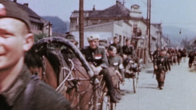vídeos de stock, filmes e b-roll de surrendered german army soldiers some injured riding in horsedrawn carts and walking through village street / czechoslovakia - veículo puxado a cavalo